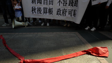 "Protesters carry a banner with Chinese reads ""Do not trample on press freedom"" next to a red ribbon symbolising the bottom line of the Chinese Communist Party during a protest in Hong Kong."