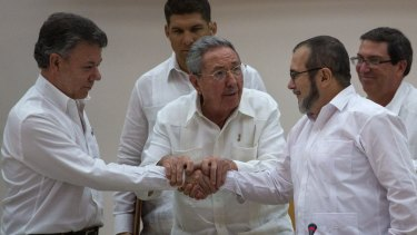 Cuban President Raul Castro, center, encourages Colombian President Juan Manuel Santos, left, and then FARC Commander Rodrigo Londono to shake hands after the signing of the peace accord in 2015.