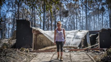 Juvette Jory looks at the rubble of her family home in Tathra