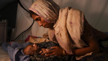 Laila Begum holds the hand of her malnourished, 40-day old son, Mohammed Ifran, as he receives treatment at the Red Cross Field Hospital in Kutupalong refugee camp.