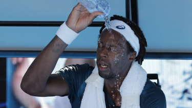 France's Gael Monfils douses himself with water due to the searing heat on court.