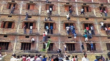 Indians climb the wall of a building to help students cheat, including their own children, appearing in an exam in 2015.