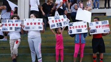 A group of people hold signs that read 'Guns Down Test Scores UP' during a protest against guns outside a federal courthouse in Florida.