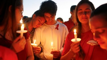 Students gather during a vigil at Pine Trails Park for the victims of Wednesday's shooting at Marjory Stoneman Douglas High School in Florida.