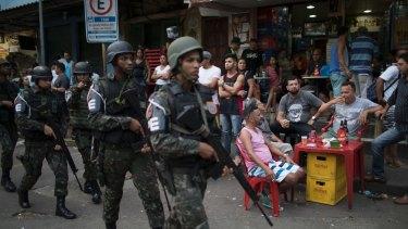 Soldiers patrol the Rocinha slum of Rio de Janeiro last year.