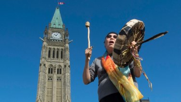 "Marcia Brown Martel sings outside Canada's parliament  in October following the announcement of  compensation for  victims of  the ""Sixties Scoop"", during which Indigenous Canadians were taken from their homes and adopted into non-Indigenous families."