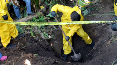 A man digs up a clandestine grave in Xalisco, Nayarit state, Mexico in which  at least 33 bodies were found.  Authorities believe they were probably involved in the drug trade.