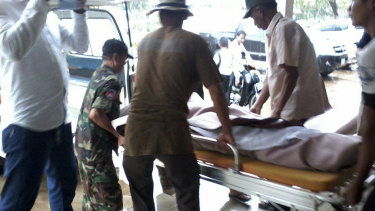 Men help carry an unidentified individual on a gurney at the local provincial hospital of Kampong Speu province.