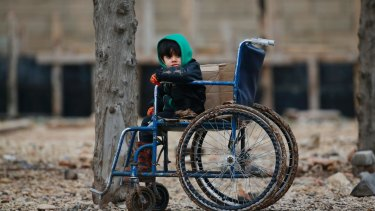 A Syrian child sits on a wheelchair after he and his family crossed into Turkey at the Oncupinar border crossing with Syria.