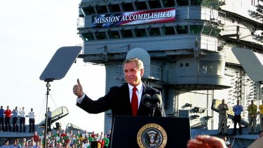 "President Bush flashes a ""thumbs-up"" after declaring the end of major combat in Iraq as he speaks aboard the aircraft carrier USS Abraham Lincoln off the California coast, ons May 1, 2003."