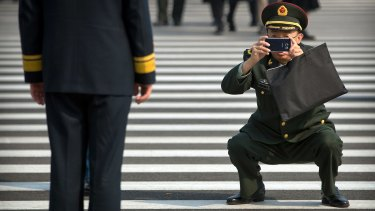 A military officer takes a smartphone photo of a fellow officer before a plenary session of the Chinese People's Political Consultative Conference.