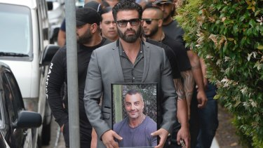 "One man carried a framed photo of Mahmoud ""Mick"" Hawi at the funeral."