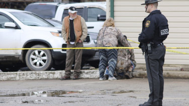 An officer stands guard as people comfort each other near the scene of a fatal shooting at a car wash in Pennsylvania.