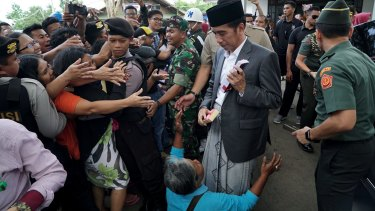 A woman cries at the feet of president Joko Widodo when complaining that her home has been destroyed in a land dispute.