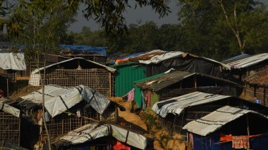A woman holds a bucket of clothes as she stands among the shelters in Kutupalong refugee camp in Bangladesh.
