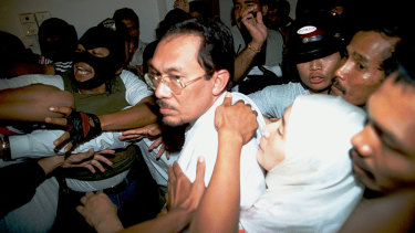 September 1998: Anwar Ibrahim's wife Wan Azizah Wan Ismail holds on to him as he is arrested at home by masked officers.