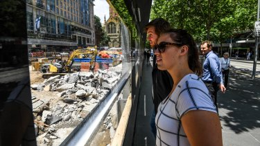 Passers-by watch as the City Square site is excavated to make way for  the underground Town Hall Station.