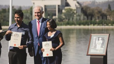 Prime Minister Malcolm Turnbull presents citizenship certificates in Canberra.