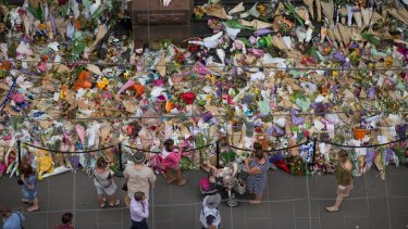 People lay flowers at the memorial to the victims of the Bourke Street attack.