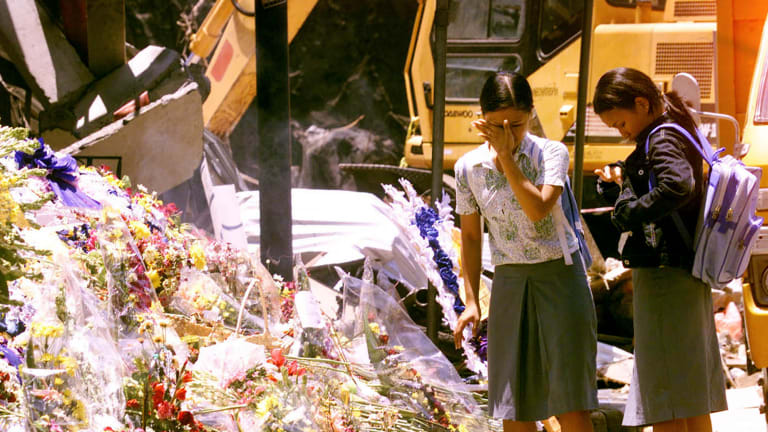Indonesian students place flowers at the bomb blast area in Kuta on October 17, 2002.