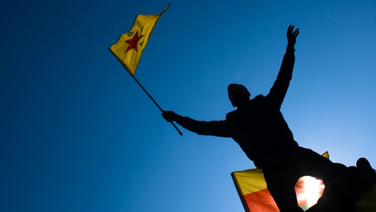 A man waves a flag with Kurdish symbols as he attends a demonstration of some thousand protesters against the Turkish offensive targeting Kurds in  northern Syria, in Berlin last week.