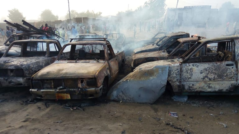 People stand behind burnt out cars following an attack by Boko Haram at a car park in Maiduguri, Nigeria.