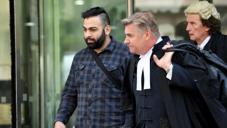 Adem Arpaci leaves the County Court with his lawyer during the first trial last year.