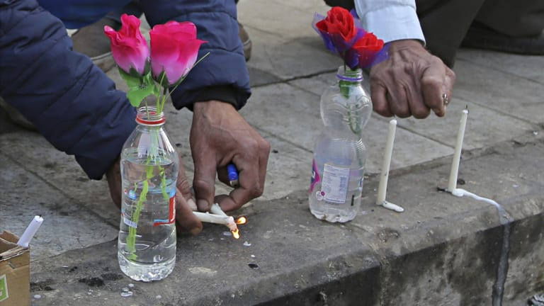 People light candles at the site of twin suicide bombings in Baghdad.