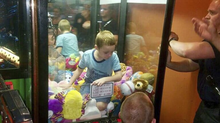 Fire fighters attempting to rescue a boy who crawled inside a claw-style vending machine in Florida.