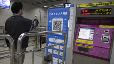 A commuter in Wuhan scans his health pass for the all-clear to ride the metro system.