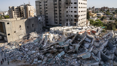 People walk past view rubble of the al-Jalaa building destroyed in a previous air strike following a ceasefire reached after an 11-day war between Gaza's Hamas rulers and Israel, in Gaza City.