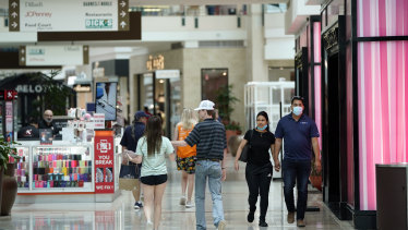 Even after re-opening the public has hesitated. Some shoppers wear masks as they walk through a mall in Woodlands, Texas.