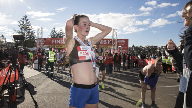 Ellie Pashley catches  her breath after fbeing the first female competitor to finish the 2018 City to Surf on 12 August 2018.