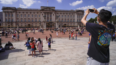 A man takes a picture of Buckingham Palace in London. The pandemic meant less revenue from tourists for the royal coffers.