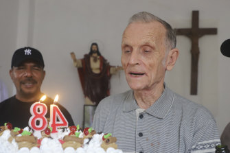 Now-defrocked Catholic priest Richard Daschbach, centre, is presented a cake during his 84th birthday in Dili in January.