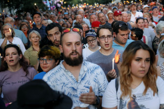 Mourners sing at a vigil in Dayton, Ohio.
