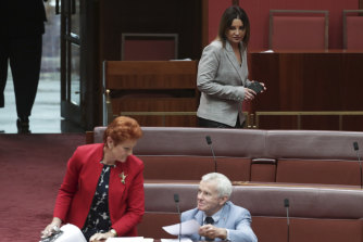 Senator Jacqui Lambie walks past Senators Pauline Hanson and Malcolm Roberts.