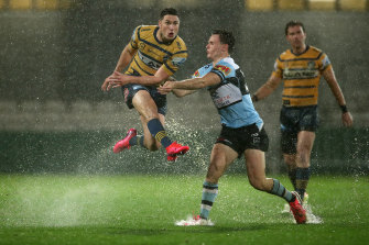 Parramatta playmaker Mitchell Moses gets a kick away in monsoonal conditions at Jubilee.