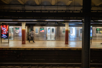 A commuter wearing a protective mask walks past a train on a subway platform in New York.
