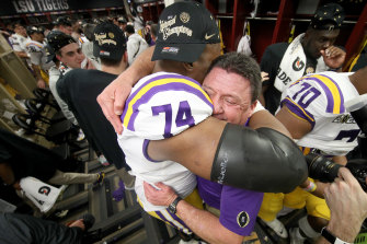 LSU head coach Ed Orgeron hugs offensive tackle Badara Traore in the winning change-room.