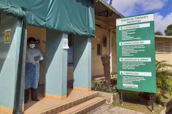 A nurse stands outside Tamara Twomey hospital in Suva, Fiji. A growing COVID outbreak has stretched the island nation's health system.