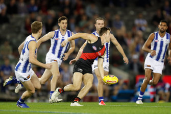 Zach Merrett looks to get the ball away for the Bombers.
