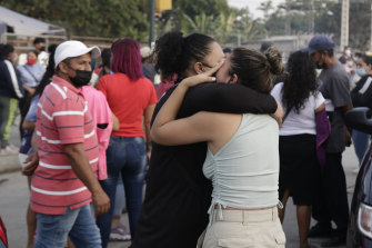 Women hug while waiting for news about their relatives who are inmates at the prison.