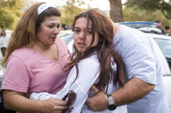 Keegan Burns, 16, seeks the comfort of her parents Mirasol and Jim following the shooting at Santa Clarita.