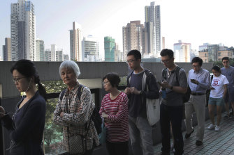 People line up to vote outside of a polling place in Hong Kong on Sunday.