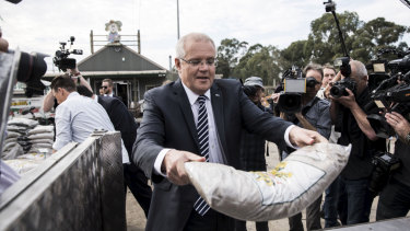 Prime Minister Scott Morrison moves some mulch at Daisy's Garden Supplies in Ringwood on Monday.