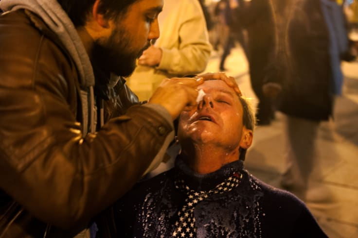 A protester receives help washing pepper spray out of his eyes on the night of US President Donald Trump's inauguration.