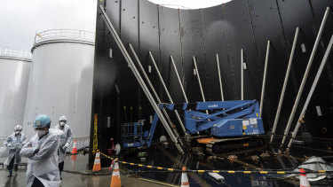 A media tour passes the Tokyo Electric Power Co's storage tank for radioactive water under construction at the Fukushima Dai-ichi nuclear power plant on January 29. The plant was wrecked by an earthquake and tsunami in 2011.