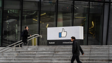A pedestrian passes the entrance to the Facebook.