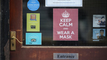 A 'Keep Calm And Wear A Face Mask' sign adorns a door in central Liverpool.